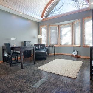 他の地域の巨大なコンテンポラリースタイルのおしゃれな書斎 (クッションフロア、自立型机、黒い床) の写真
