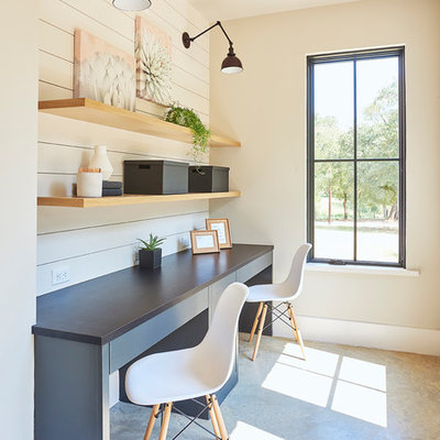 Transitional built-in desk concrete floor and gray floor study room photo in Dallas with white walls