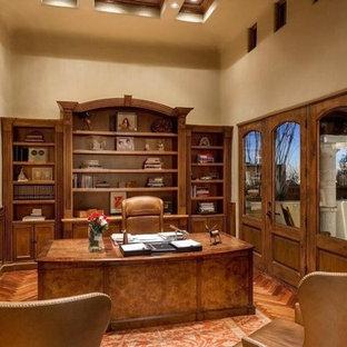 Esempio di un ampio studio mediterraneo con libreria, pareti gialle, moquette, nessun camino, scrivania incassata, cornice del camino in pietra e pavimento marrone