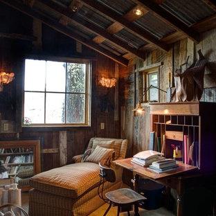 Exempel på ett mellanstort rustikt hemmabibliotek, med bruna väggar, betonggolv och ett fristående skrivbord