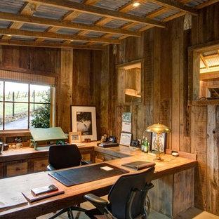 Ejemplo de despacho rústico, de tamaño medio, sin chimenea, con paredes marrones, suelo de cemento, escritorio empotrado y suelo gris