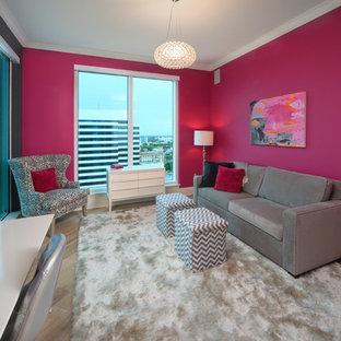 Inredning av ett modernt arbetsrum, med rosa väggar, ett fristående skrivbord och mellanmörkt trägolv