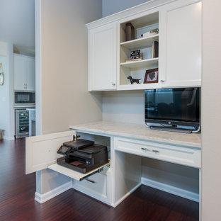 Immagine di un piccolo ufficio design con pareti grigie, parquet scuro e scrivania incassata