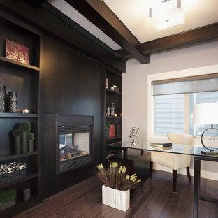 На фото: рабочее место в стиле неоклассика (современная классика) с серыми стенами, темным паркетным полом, двусторонним камином, фасадом камина из дерева и отдельно стоящим рабочим столом с