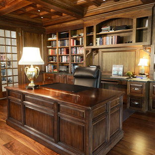 Design ideas for a mid-sized arts and crafts home office in Other with a library, brown walls, medium hardwood floors, no fireplace, a freestanding desk and brown floor.