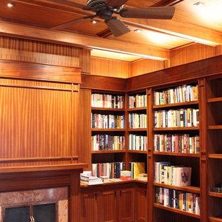 Ispirazione per un grande studio american style con libreria, pareti marroni, pavimento in legno massello medio, camino classico, cornice del camino in pietra, scrivania autoportante e pavimento marrone