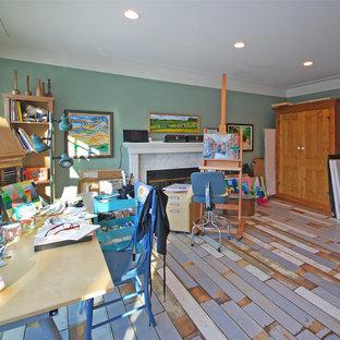 Immagine di una grande stanza da lavoro chic con pareti verdi, pavimento in legno verniciato, camino classico, cornice del camino in pietra e scrivania autoportante