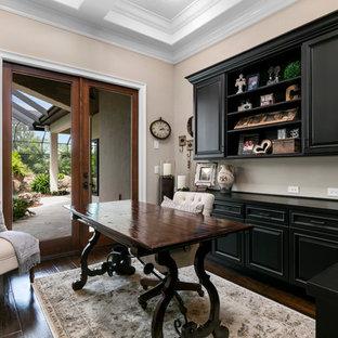 Exempel på ett mellanstort medelhavsstil hemmabibliotek, med beige väggar, mörkt trägolv och ett fristående skrivbord