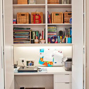 Idéer för ett litet modernt arbetsrum, med vita väggar, ett inbyggt skrivbord och mellanmörkt trägolv