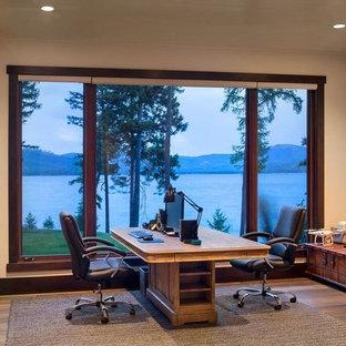 Modelo de despacho rústico, de tamaño medio, con paredes beige, suelo de madera oscura, chimenea de doble cara, marco de chimenea de piedra, escritorio independiente y suelo marrón