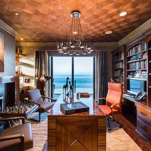 ロサンゼルスの大きいトロピカルスタイルのおしゃれな書斎 (濃色無垢フローリング、横長型暖炉、自立型机、グレーの壁、石材の暖炉まわり、茶色い床) の写真