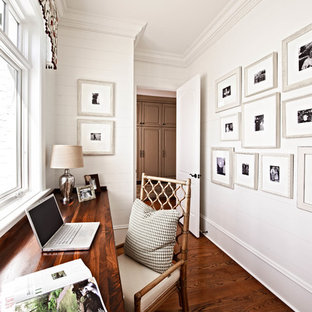 Example of a classic built-in desk dark wood floor home office design in Charlotte with white walls