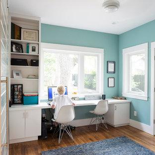 Inspiration för små klassiska hemmabibliotek, med ett inbyggt skrivbord, blå väggar, mellanmörkt trägolv och brunt golv