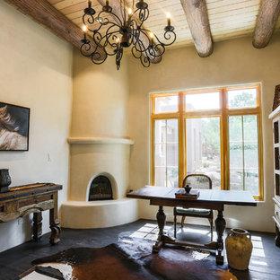 アルバカーキのサンタフェスタイルのおしゃれなホームオフィス・書斎 (ベージュの壁、濃色無垢フローリング、コーナー設置型暖炉、自立型机、黒い床) の写真