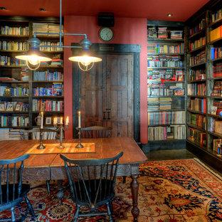 Foto di uno studio rustico con pareti rosse, scrivania autoportante, parquet scuro e libreria