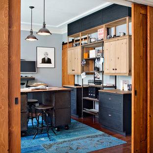 Cette image montre un bureau urbain de taille moyenne et de type studio avec un sol en bois brun, aucune cheminée, un mur gris et un bureau indépendant.