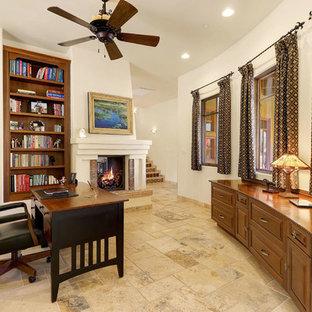 Immagine di un ufficio di medie dimensioni con pareti bianche, cornice del camino in intonaco, scrivania autoportante, pavimento multicolore e camino bifacciale