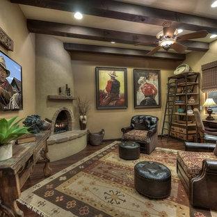 フェニックスの大きいサンタフェスタイルのおしゃれな書斎 (ベージュの壁、濃色無垢フローリング、コーナー設置型暖炉、コンクリートの暖炉まわり、自立型机) の写真