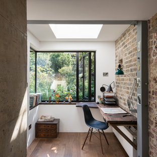 Industrial home office in London with white walls, dark hardwood floors and a built-in desk.