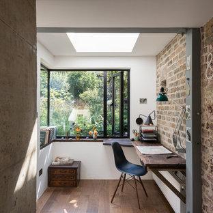 Industrial Arbeitszimmer mit weißer Wandfarbe, dunklem Holzboden und Einbau-Schreibtisch in London