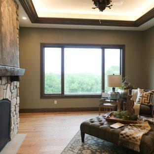 Modelo de despacho grande con paredes verdes, suelo de madera en tonos medios, chimenea de doble cara, escritorio independiente y suelo marrón