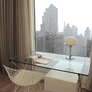 Esempio di un piccolo ufficio moderno con parquet chiaro, scrivania autoportante, pareti bianche e pavimento marrone