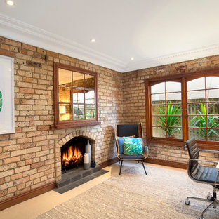 Eclectic study room in Sydney with carpet, a standard fireplace, a brick fireplace surround, a freestanding desk, beige floor and brown walls.