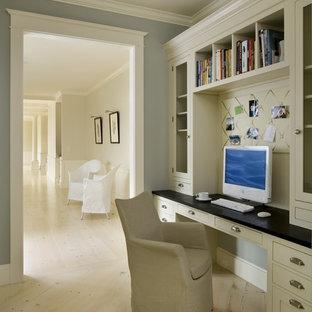 Ejemplo de despacho clásico con paredes grises, suelo de madera clara, escritorio empotrado y suelo beige
