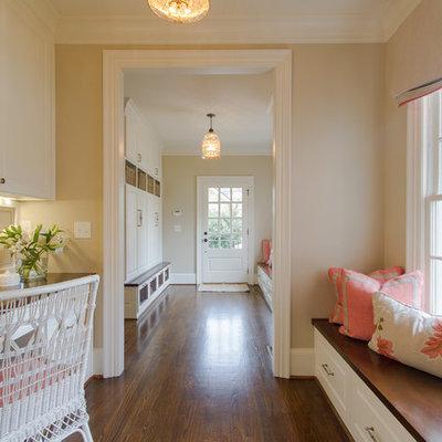 Elegant built-in desk brown floor home office photo in Atlanta with beige walls