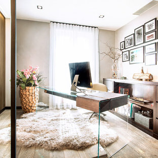 Medium sized contemporary study in London with beige walls, light hardwood flooring, a freestanding desk and beige floors.