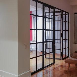 Idéer för att renovera ett mellanstort funkis hemmabibliotek, med röda väggar, mörkt trägolv och brunt golv