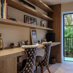 ロンドンの小さいトランジショナルスタイルのおしゃれなホームオフィス・仕事部屋 (ベージュの壁、淡色無垢フローリング、造り付け机、グレーの床) の写真