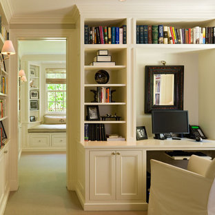 Example of a classic built-in desk home office design in Denver with beige walls