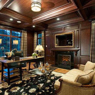 Klassisk inredning av ett stort arbetsrum, med mellanmörkt trägolv, en standard öppen spis, ett fristående skrivbord, bruna väggar och en spiselkrans i trä