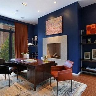 Ispirazione per un grande ufficio design con pareti blu, pavimento in bambù, camino classico, cornice del camino in pietra e scrivania autoportante