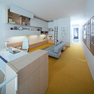 バンクーバーの大きいモダンスタイルのおしゃれな書斎 (白い壁、カーペット敷き、暖炉なし、造り付け机、黄色い床) の写真