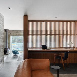 Diseño de despacho actual, de tamaño medio, con suelo de cemento, chimenea de esquina, marco de chimenea de hormigón, escritorio empotrado y suelo gris