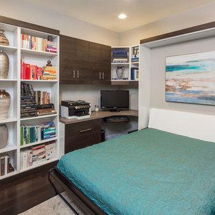 Modern inredning av ett stort arbetsrum, med ett bibliotek, beige väggar, mörkt trägolv, ett inbyggt skrivbord och brunt golv