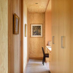 シアトルのコンテンポラリースタイルのおしゃれなホームオフィス・書斎 (茶色い壁、造り付け机、茶色い床、板張り天井、板張り壁) の写真