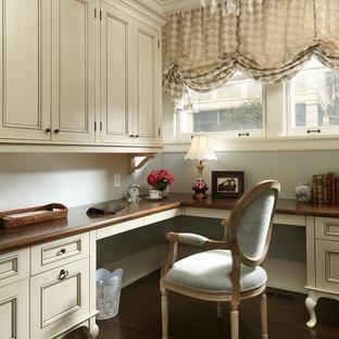 Elegant built-in desk dark wood floor and brown floor home office photo in Minneapolis with gray walls