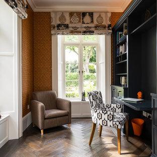 Ejemplo de despacho tradicional renovado, grande, con escritorio empotrado, parades naranjas, suelo de madera en tonos medios y suelo marrón