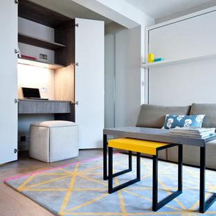 Создайте стильный интерьер: маленький рабочее место в современном стиле с серыми стенами, паркетным полом среднего тона и встроенным рабочим столом без камина - последний тренд