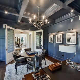 Exempel på ett stort klassiskt hemmabibliotek, med blå väggar, mörkt trägolv och ett fristående skrivbord