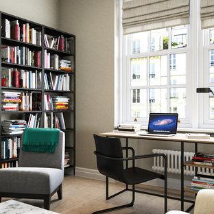 Study room - transitional freestanding desk light wood floor study room idea in London with beige walls