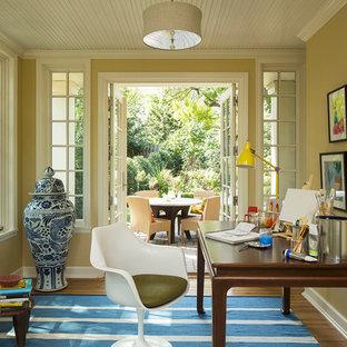 На фото: кабинет в стиле фьюжн с желтыми стенами, темным паркетным полом и отдельно стоящим рабочим столом