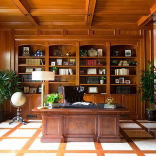 Imagen de despacho tradicional con paredes marrones, escritorio independiente y suelo multicolor