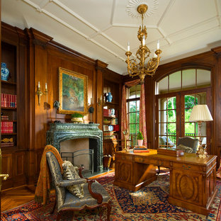 Example of a classic freestanding desk medium tone wood floor home office design in Dallas with a standard fireplace