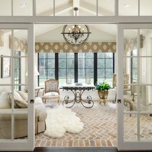 ヒューストンの広いシャビーシック調のおしゃれな書斎 (白い壁、レンガの床、自立型机、マルチカラーの床) の写真