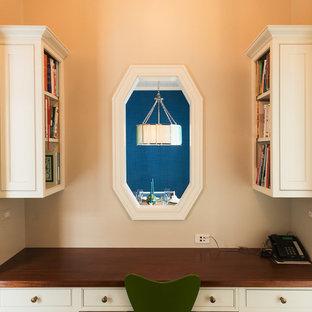 Exemple d'un grand bureau chic de type studio avec un mur beige, un sol en bois brun, une cheminée standard et un manteau de cheminée en pierre.