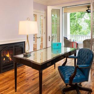 Ispirazione per uno studio tradizionale di medie dimensioni con pareti viola, pavimento in legno massello medio, camino classico e scrivania autoportante